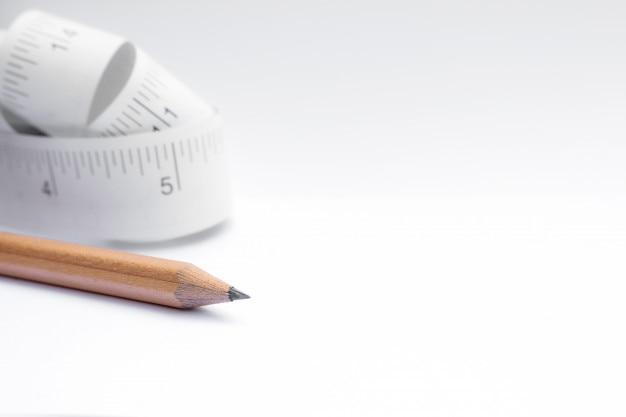 Nahaufnahme bleistift und papiermaßband rollen auf weißem hintergrund mit kopienraum