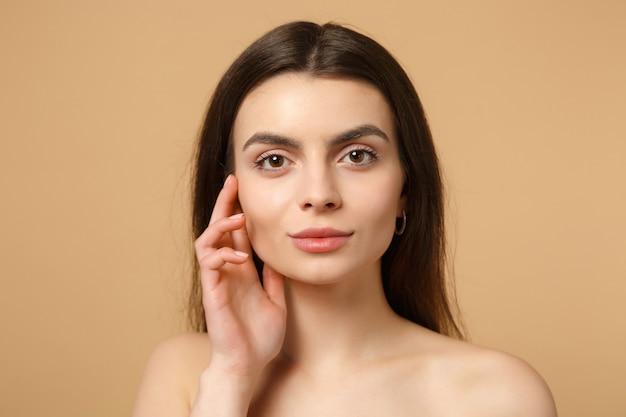 Nahaufnahme brünette halbnackte frau 20er jahre mit perfekter haut, nacktes make-up isoliert auf beige pastellfarbener wand, porträt. konzept für kosmetische verfahren der hautpflege im gesundheitswesen.