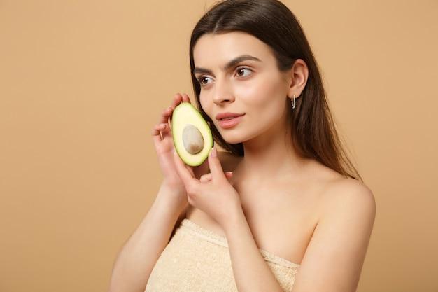 Nahaufnahme brünette halbnackte frau mit perfekter haut nackt make-up hält avocado isoliert auf beige pastellfarbener wand