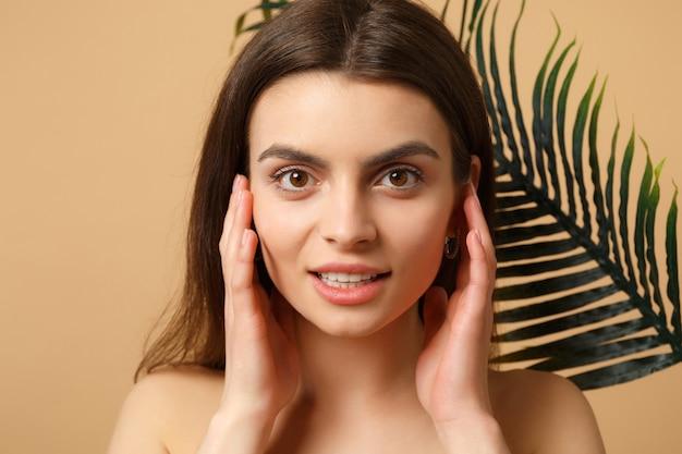 Nahaufnahme brünette halbnackte frau mit perfekter haut, nacktem make-up und palmblatt isoliert auf beige pastellfarbener wand