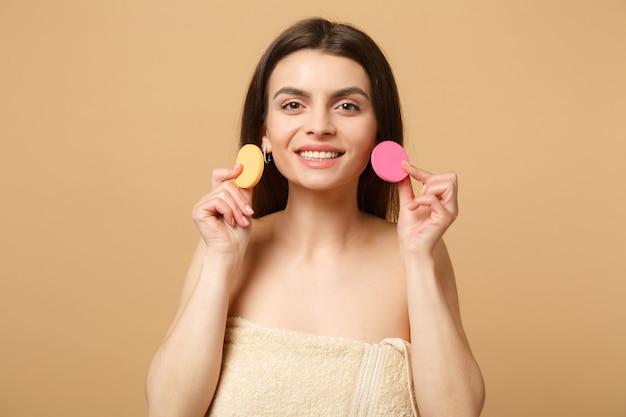 Nahaufnahme brünette halbnackte frau mit perfekter haut, nacktes make-up entfernen isoliert auf beige pastellfarbener wand