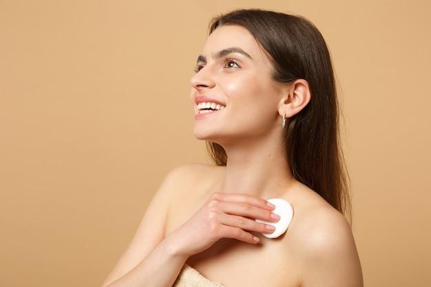 Nahaufnahme brünette halbnackte frau mit perfekter haut, nacktes make-up isoliert auf beige pastellfarbener wand