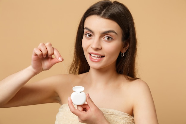 Nahaufnahme brünette halbnackte frau mit perfekter haut, nacktes make-up mit zahnseide isoliert auf beige pastellfarbener wand