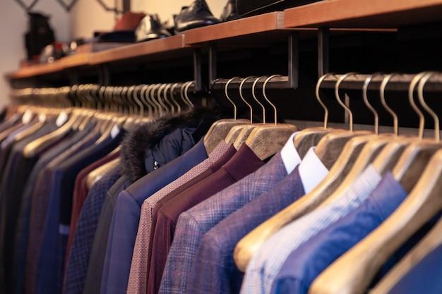 Nahaufnahme bunte männliche, weibliche kleidung in der boutique, die an kleiderbügeln, kleiderständer auf metallständer hängt. konzept eröffnung luxusgeschäft, einkaufszentrum, ladenverkauf, modegeschäft, second-hand-outlet.