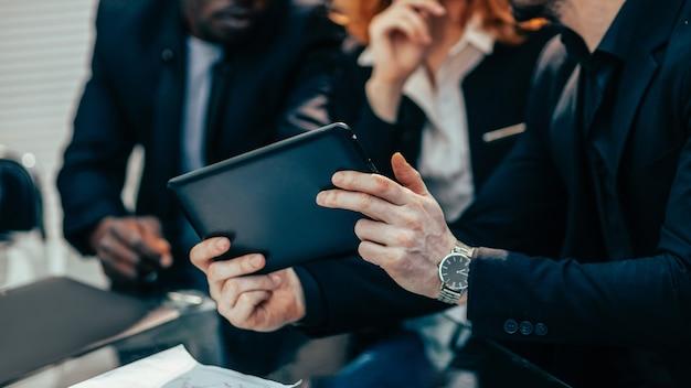 Nahaufnahme. business-team mit blick auf den bildschirm eines digitalen tablets. mensch und technik