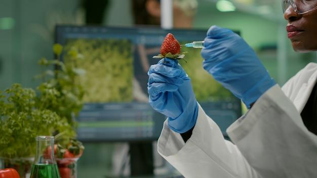 Nahaufnahme chemiker wissenschaftler injizieren naturerdbeere mit chemischen pestiziden
