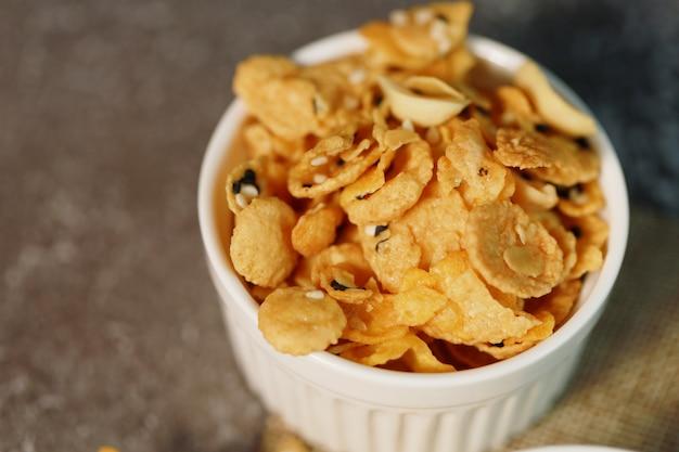 Nahaufnahme cornflakes körner und nüsse in kleinen weißen schüssel das gute essen für die ernährung in milchprodukten für die frische ernährung und gut gesund im alltag.
