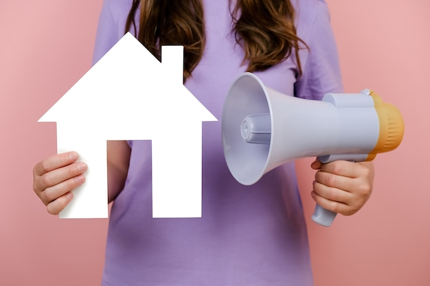 Nahaufnahme der abgeschnittenen frau, die an weißbuchhaus und megaphon hält, wohnungsbaudarlehensauktionsverkaufsmiete-eigenschaftsinformationen, einzeln über rosa studiohintergrundwand immobilienmarketing und hypothekarkonzept