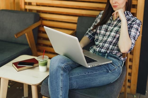 Nahaufnahme der abgeschnittenen frau im straßencafé aus holz im freien, die in freizeitkleidung sitzt und an einem modernen laptop-pc arbeitet?