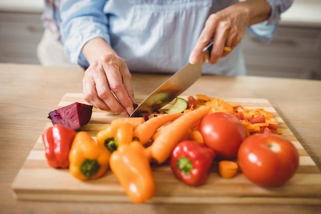 Nahaufnahme der älteren frau gemüse in der küche hackend