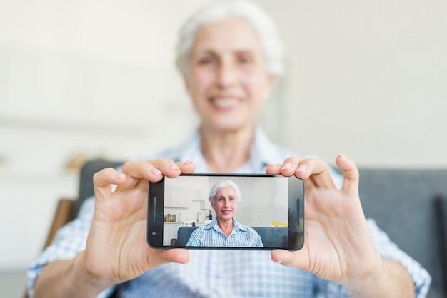Nahaufnahme der älteren frau ihr foto auf smartphone zeigend