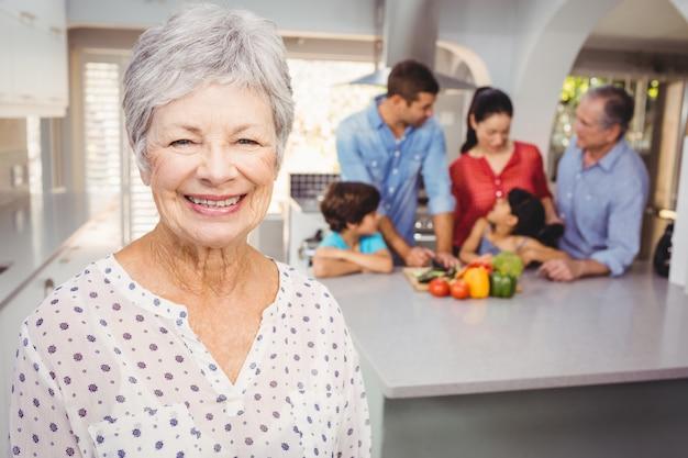Nahaufnahme der älteren frau mit der familie, die lebensmittel im hintergrund zubereitet