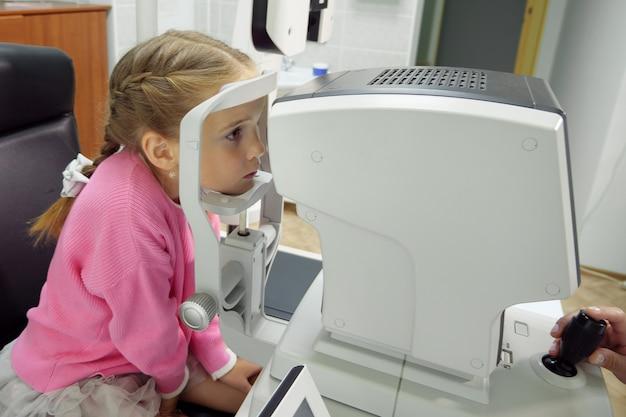 Nahaufnahme der ärztin, die mit der refraktometermaschine arbeitet. ein kleines mädchen lässt ihre augen testen.