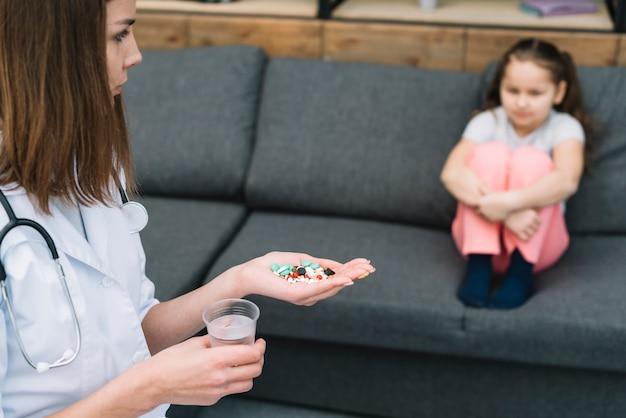 Nahaufnahme der ärztin medizin und glas wasser halten das mädchen betrachtend, das auf sofa sitzt