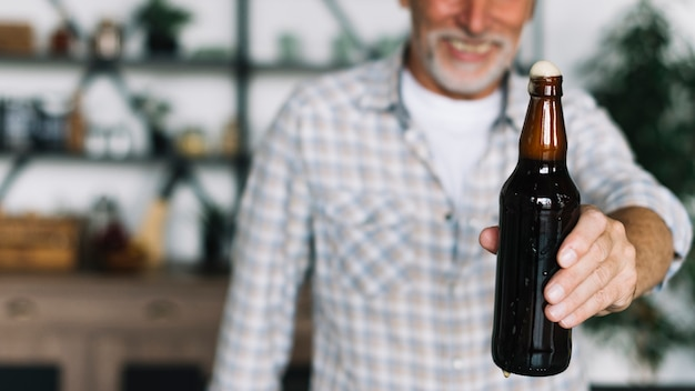 Nahaufnahme der anbietenflasche des älteren mannes