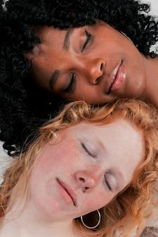 Nahaufnahme der angemessenen und dunkelhäutigen jungen frau, die ihren kopf auf einander schlafend lehnt