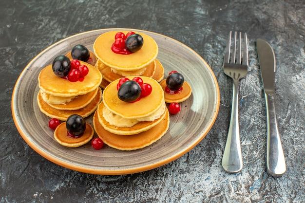 Nahaufnahme der ansicht von fruchtpfannkuchen neben gabel und messer