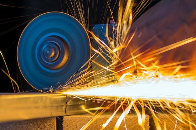 Nahaufnahme der arbeiterhände, die metall mit schleifmaschine schneiden. funken beim schleifen von eisen. geringe schärfentiefe