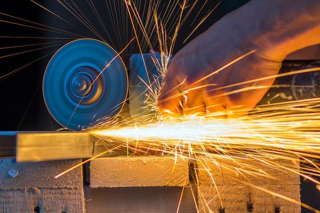 Nahaufnahme der arbeiterhände, die metall mit schleifmaschine schneiden.