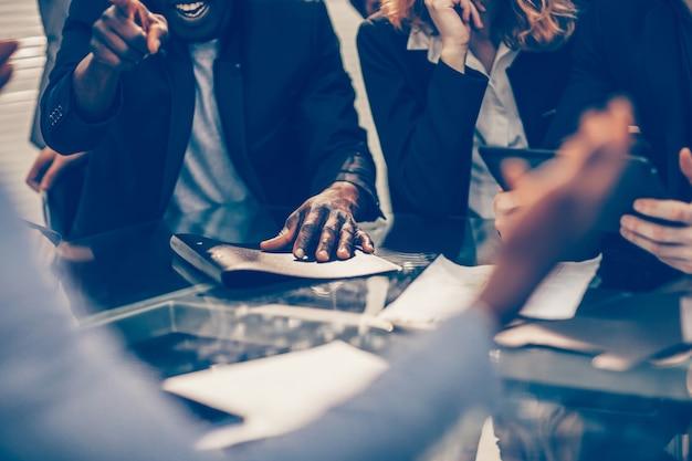 Nahaufnahme der arbeitsgruppe, die neue ideen bei einem bürobesprechungsfoto mit exemplar bespricht
