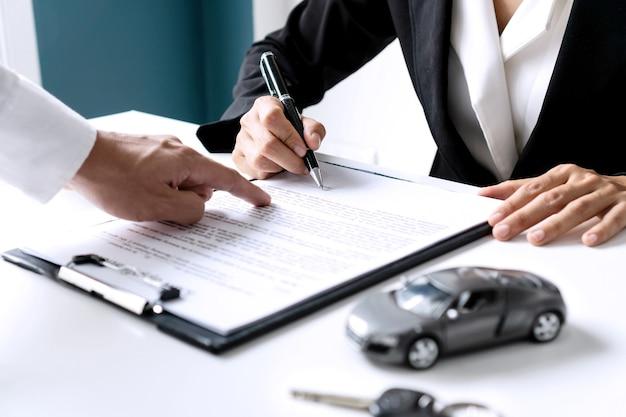 Nahaufnahme der asiatischen frau, die autoversicherungsdokument oder mietpapiervertrag oder -vereinbarung unterzeichnet