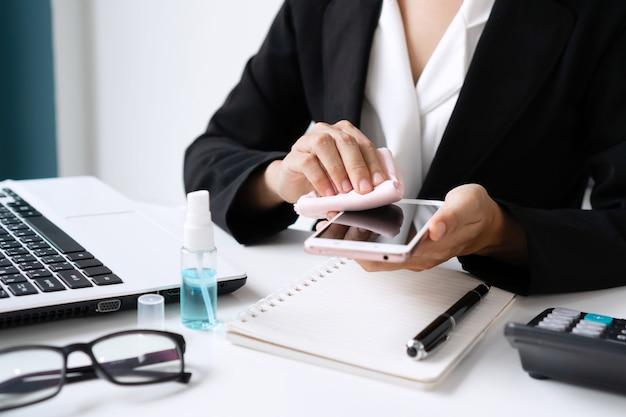 Nahaufnahme der asiatischen frau, die smartphone durch alkoholspray über einem arbeitstisch im büro reinigt