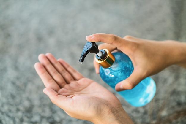 Nahaufnahme der asiatischen frau, die vor der arbeit während des corona-virus den handdesinfektionsgel-pumpspender zum waschen verwendet