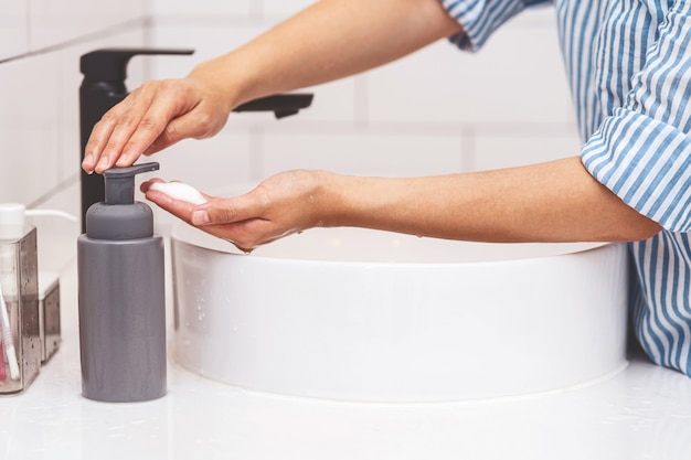 Nahaufnahme der asiatischen frau, die zu hause im badezimmer mit wasser aus dem wasserhahn stößt und sich wäscht