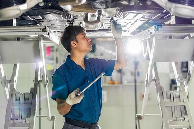 Nahaufnahme der asiatischen mechanikerhand, die unter dem auto im wartungsservicezentrum repariert