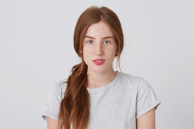 Nahaufnahme der attraktiven friedlichen rothaarigen jungen frau mit sommersprossen fühlt sich zuversichtlich