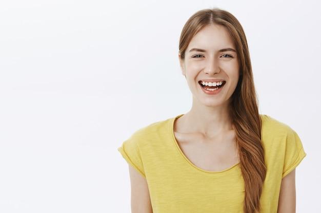 Nahaufnahme der attraktiven sorglosen frau, die glücklich lacht und lächelt