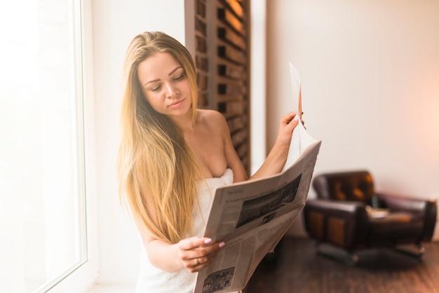 Nahaufnahme der attraktiven zeitung der jungen frau lese