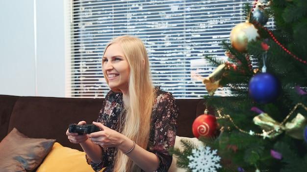 Nahaufnahme der aufgeregten frau verliert spiel auf joystick nahe dem weihnachtsbaum
