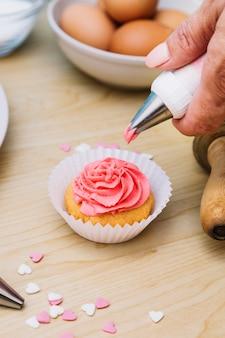 Nahaufnahme der bäckerhandbutterbuttercreme, die auf kleinem kuchen über dem hölzernen schreibtisch bereift