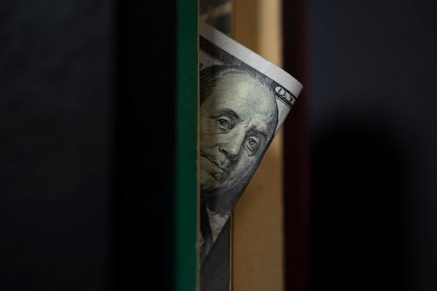 Nahaufnahme der banknote mit benjamin franklin späht aus einem buch