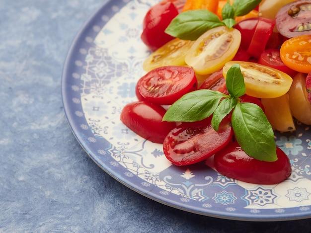 Nahaufnahme der basilikumblätter rote und gelbe kirschtomaten in einem salat