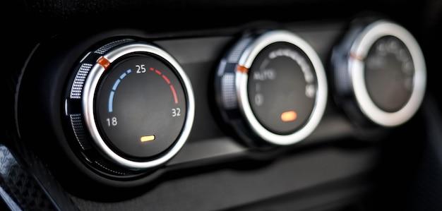 Nahaufnahme der bedientasten der autoklimaanlage. es gibt drei regler für die automatische klimaanlage, temperaturregler.