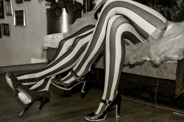 Nahaufnahme der beine des zirkusartisten in anzug und gestreiften rot-schwarzen strümpfen in der umkleidekabine. zirkusartist, der auf eine einladung wartet, bühne oder arena zu betreten. konzertauftritt für hintergründe