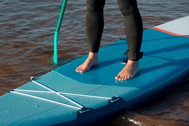 Nahaufnahme der beine, die auf dem paddleboard stehen