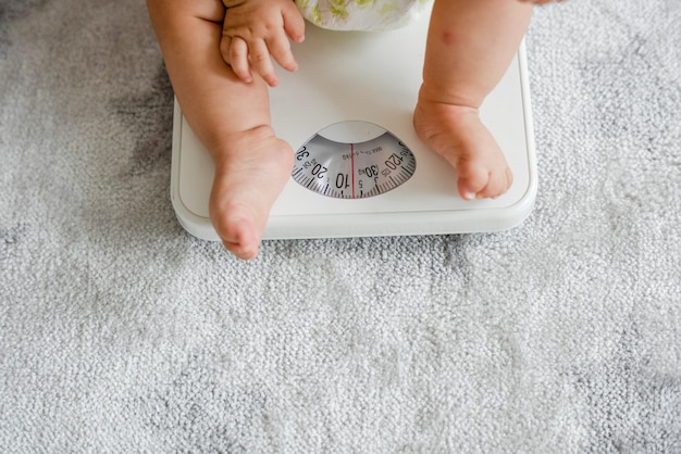 Nahaufnahme der beine eines babys auf einer wiegenden skala