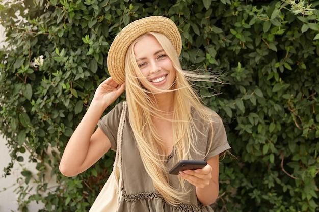 Nahaufnahme der bezaubernden jungen dame mit dem langen blonden haar im lässigen leinenkleid, das ihren hut begradigt, mit breitem lächeln schauend, telefon in der hand haltend