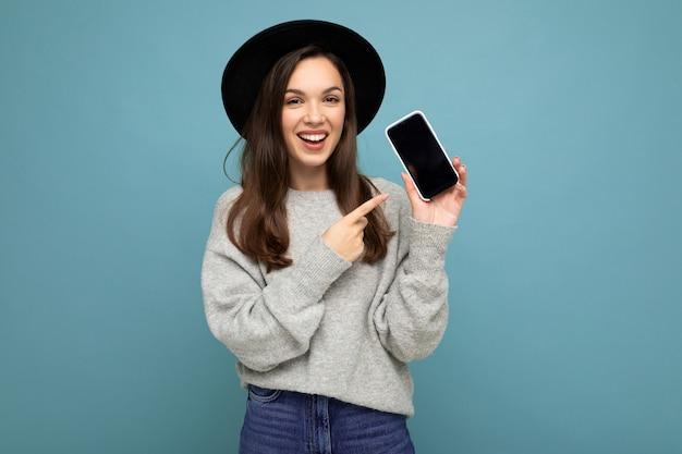 Nahaufnahme der bezaubernden jungen glücklichen frau, die schwarzen hut und grauen pullover hält telefon hält