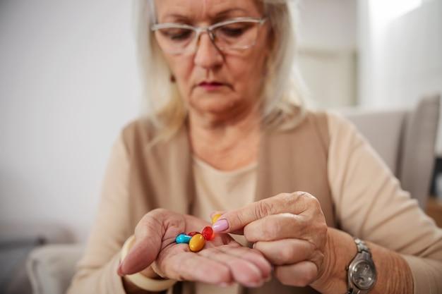 Nahaufnahme der blonden älteren frau, die zu hause sitzt und hand voll von pillen hält.