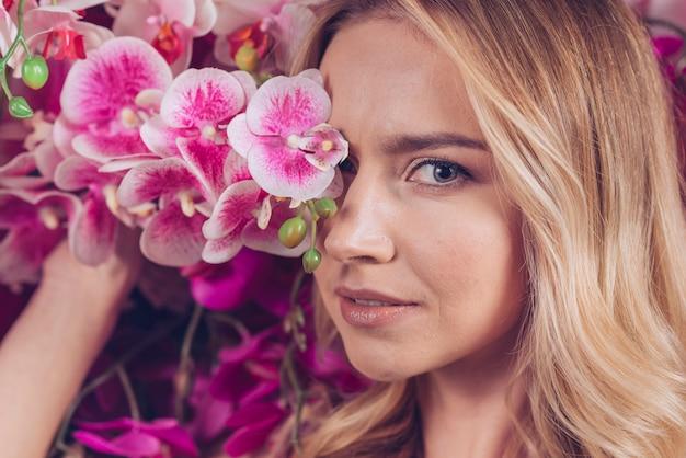 Nahaufnahme der blonden jungen frau, die ihre augen mit rosafarbener orchidee bedeckt