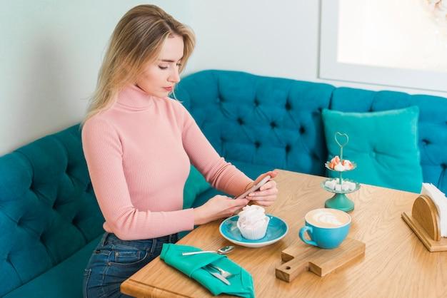 Nahaufnahme der blonden jungen frau, die mitteilung des handys im caf� simst