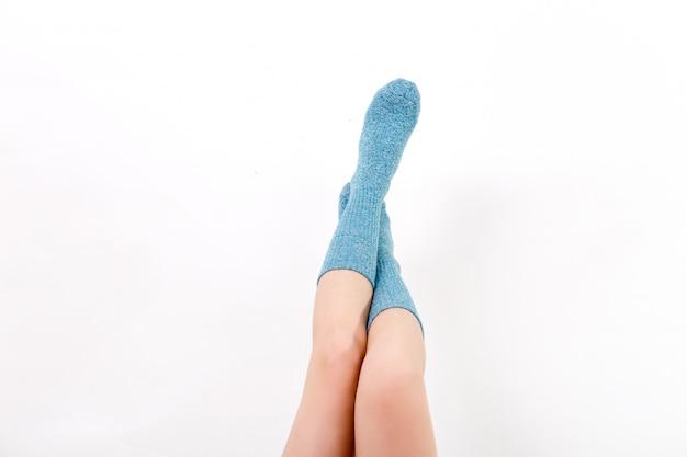 Nahaufnahme der bloßen beine einer jungen frau, die blaue socken mit seinen füßen trägt.