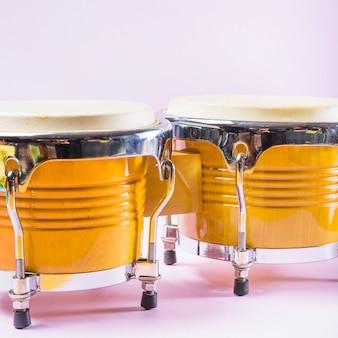 Nahaufnahme der bongotrommel auf rosa hintergrund
