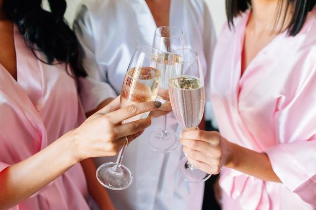 Nahaufnahme der braut und der brautjungfern, die ein glas champagner in ihrer hand halten