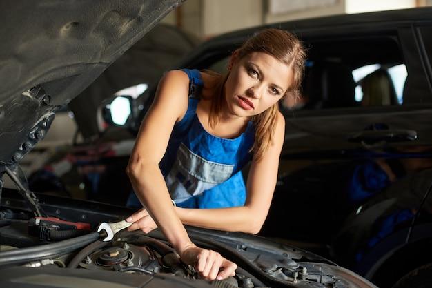 Nahaufnahme der brünetten weiblichen mechaniker, die ein auto reparieren oder inspizieren