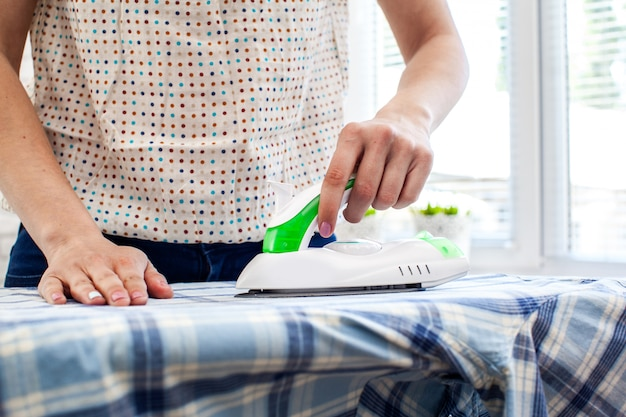 Nahaufnahme der bügelnden kleidung der frau auf bügelbrett